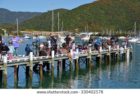 Picton, New Zealand - October 09, 2015: Dozens of keen young anglers compete in the annual  Childrens' Fishing competition held on the Waikawa Bay Jetty, Picton New Zealand.  - stock photo