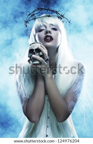 Picture a beautiful angelic long hair woman with skull - stock photo