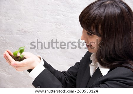 Picture about a businesswoman who keep in her hands a green sprout - stock photo