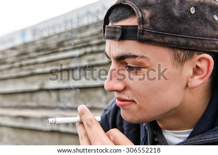 Picture about smoking. young man is laughing and smoking a cigarette outdoor. - stock photo