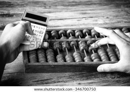picture black & white. Man's hands accounting with old abacus and hold electronic calculator. picture financial concept - stock photo
