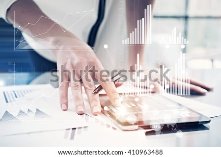 Picture female hand touching modern tablet.Investment manager working new private banking project office.Using electronic device.Graphic icons,worldwide stock exchanges interface on screen. Horizontal