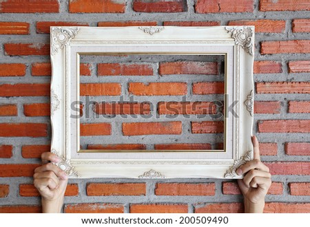 picture frame on hand , brick wall - stock photo