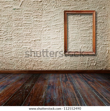 Picture frame put on wall in grunge room. - stock photo