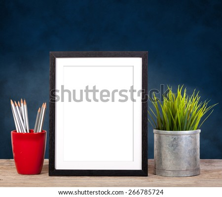 picture frame with office items and pot plant on wooden table - stock photo
