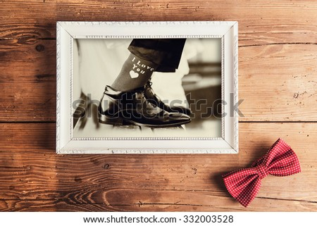 Picture frame with wedding photo. Studio shot on wooden background. - stock photo