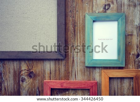 picture frames of different colors and wooden background - stock photo
