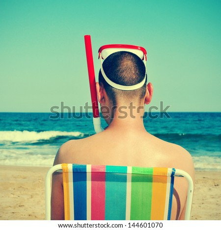 picture from the back of a man wearing a diving mask and a snorkel seated in a deckchair on the beach, with a retro effect - stock photo