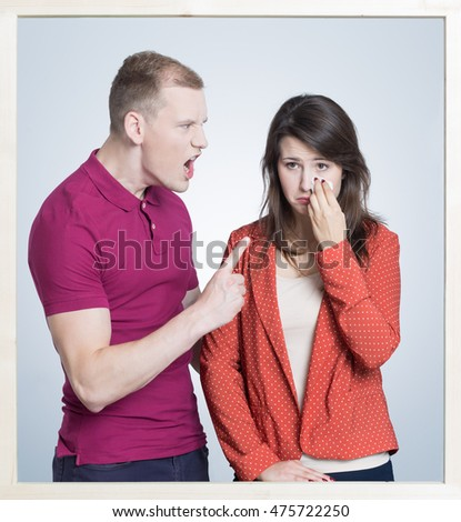 Picture in a frame of a young aggressive man shouting on a crying woman