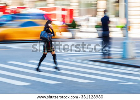 picture in motion blur of a woman crossing a street while she is phoning