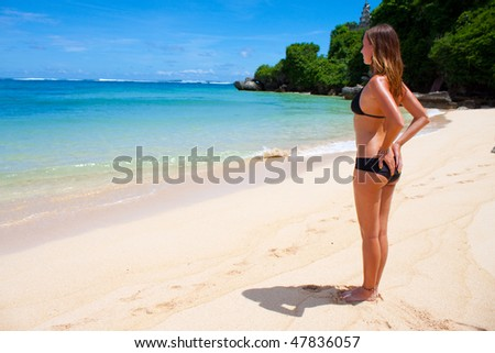 Picture of a beautiful beach in the tropics, with a woman on the beach.