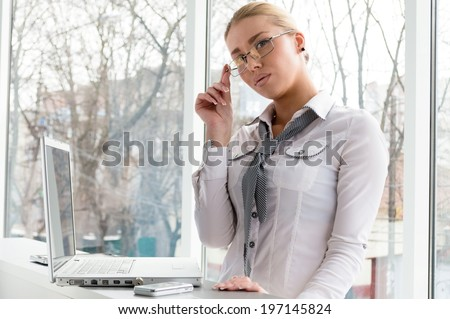 picture of a beautiful blond glamor young business woman using notebook PC computer relaxing having fun seriously looking at camera near office window background portrait - stock photo