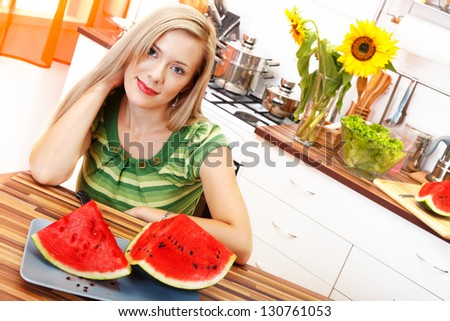 Picture of a beautiful blonde woman with watermelon sitting in the kitchen