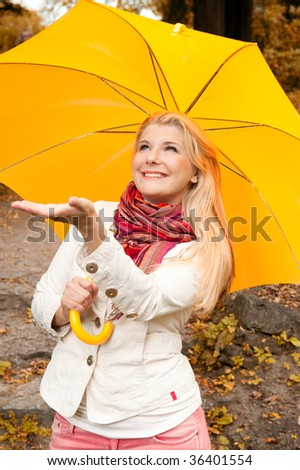 Picture of a beautiful young happy girl in an orange scarf under the yellow autumn  umbrella