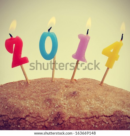 picture of a cake with number-shaped candles of different colors forming number 2014 with a retro effect - stock photo