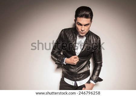 Picture of a casual young man closing his leather jacket while looking at the camera, holding his thumb in his pocket.