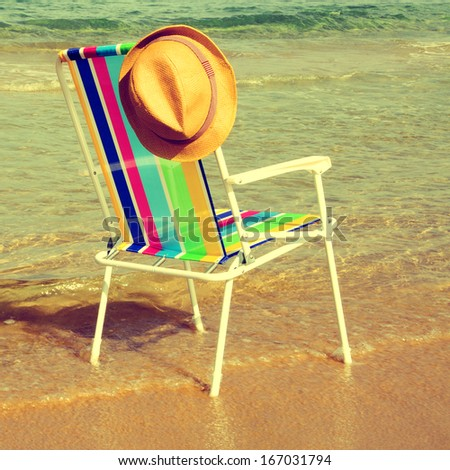 picture of a colored deckchair and a straw hat on the beach, with a retro effect - stock photo
