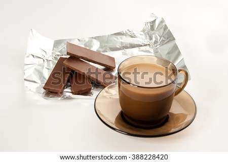 Picture of a cup of coffee and a four pieces of chocolate - stock photo