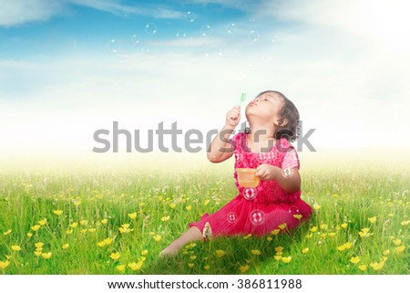Picture of a cute Asian girl sitting on the meadow while playing and blowing soap bubble, shot in springtime