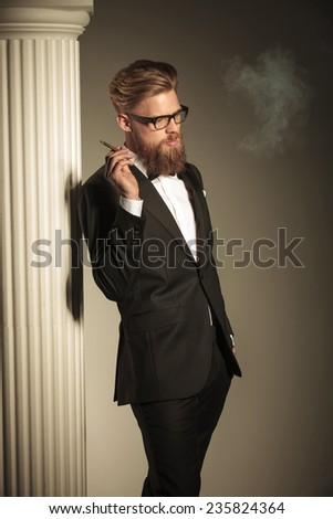 Picture of a elegant business man enjoying his cigarette while looking away from the camera with one hand in his pocket. - stock photo