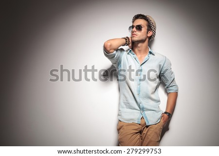 Picture of a fashion man holding his hand to his neck while leaning on a wall, looking up.