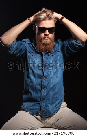 Picture of a fashion man in blue shirt wearing sunglasses sitting and looking away. On black background.
