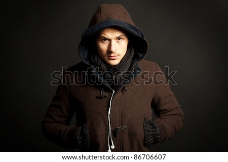 picture of a fashion man wearing a hooded coat on dark background - stock photo