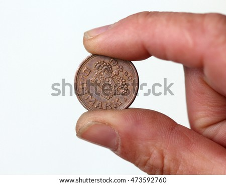 picture of a Fingers hold old coin from denmark