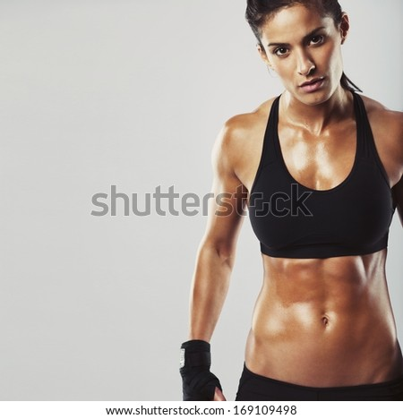 Picture of a fitness model on grey background. Young woman bodybuilder with muscular body looking at camera with copyspace - stock photo