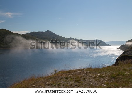 Picture of a fjord with some clouds in the middle