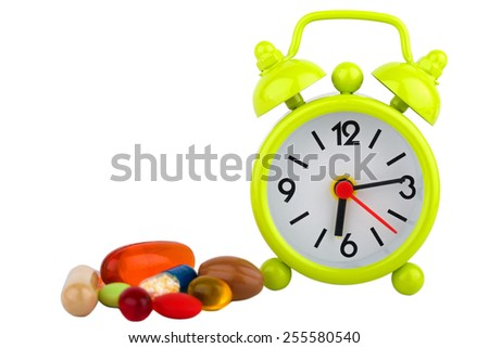 Picture of a green clock, colourful pills and capsules - stock photo