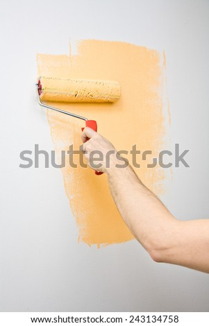 Picture of a hand painting the wall with roller - stock photo