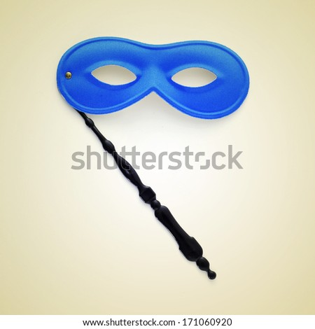 picture of a handled blue carnival mask on a beige background, with a retro effect - stock photo