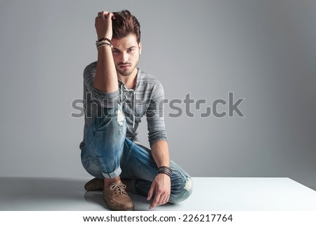 Picture of a handsome fashion man sitting on the floor while fixing his hair, looking at the camera. - stock photo