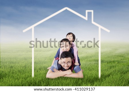 Picture of a happy Asian father and his children lying on the meadow under a house symbol