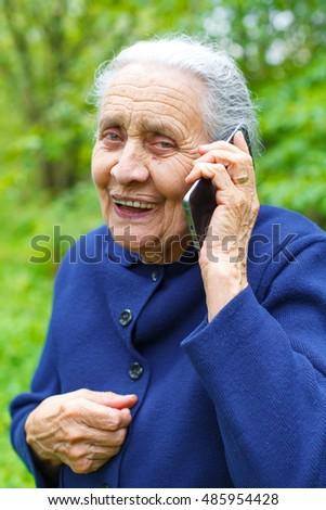 Picture of a happy old woman receiving good news by phone