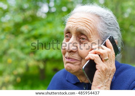 Picture of a happy old woman, talking on cell phone