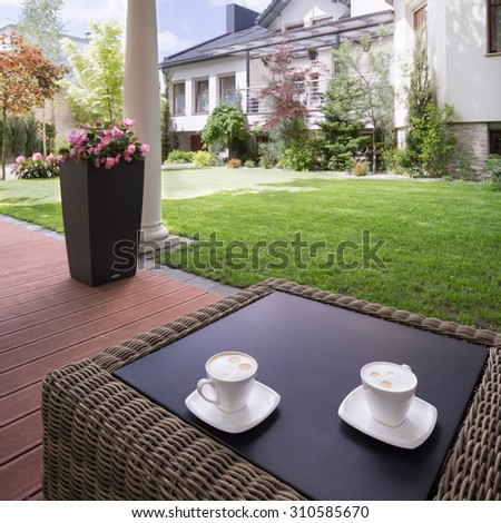 Picture of a house patio with stylish rattan table - stock photo