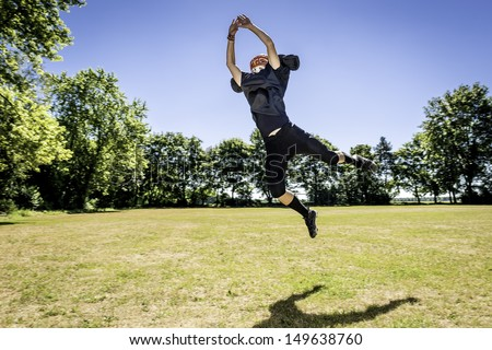 Picture of a jumping American Football Player - stock photo