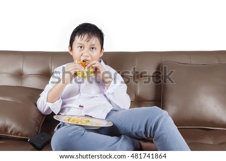 Picture of a little boy enjoying cheeseburger while sitting on the couch and watching tv