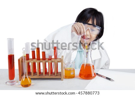 Picture of a little female chemist makes experiments with chemical liquid on the table, isolated on white background