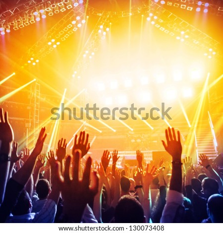 Picture of a lot of people enjoying night perfomance of famous dj, large crowd of youth dancing with raised up hands on rock concert, party in dance club, bright yellow light from stage, nightlife - stock photo