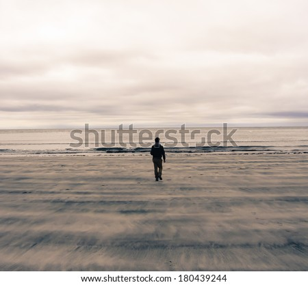 Picture of a man from behind walking on a beach in Scotland (UK). Watercolor Effect. - stock photo