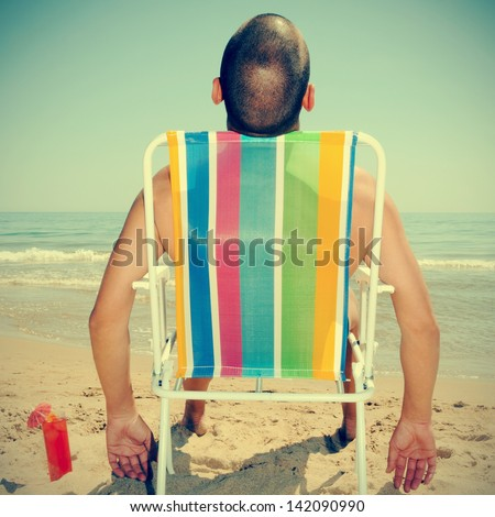 picture of a man sunbathing on a deckchair on the beach with a cocktail, with a retro effect - stock photo