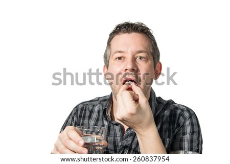 Picture of a man that is taking a painkiller - stock photo