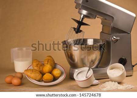 Picture of a mixer and all the ingredients to cook muffins. - stock photo