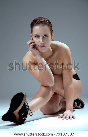 picture of a naked woman, on the floor, studio shoot