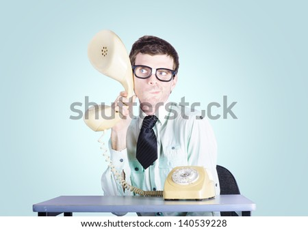 Picture of a nerd businessman sitting at an office desk holding enlarged telephone receiver to intercept competition intelligence. Market research concept