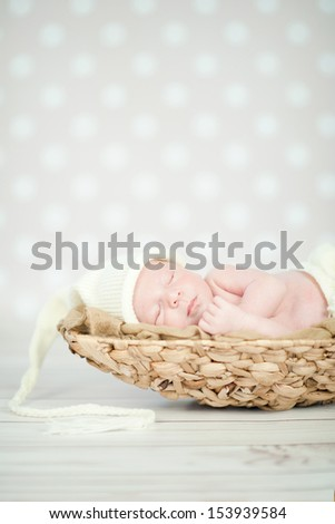 Picture of a newborn baby curled up sleeping in a basket - stock photo