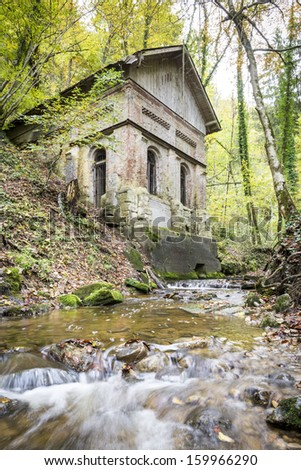 Picture of a old house and creek in a forest in autumn - stock photo